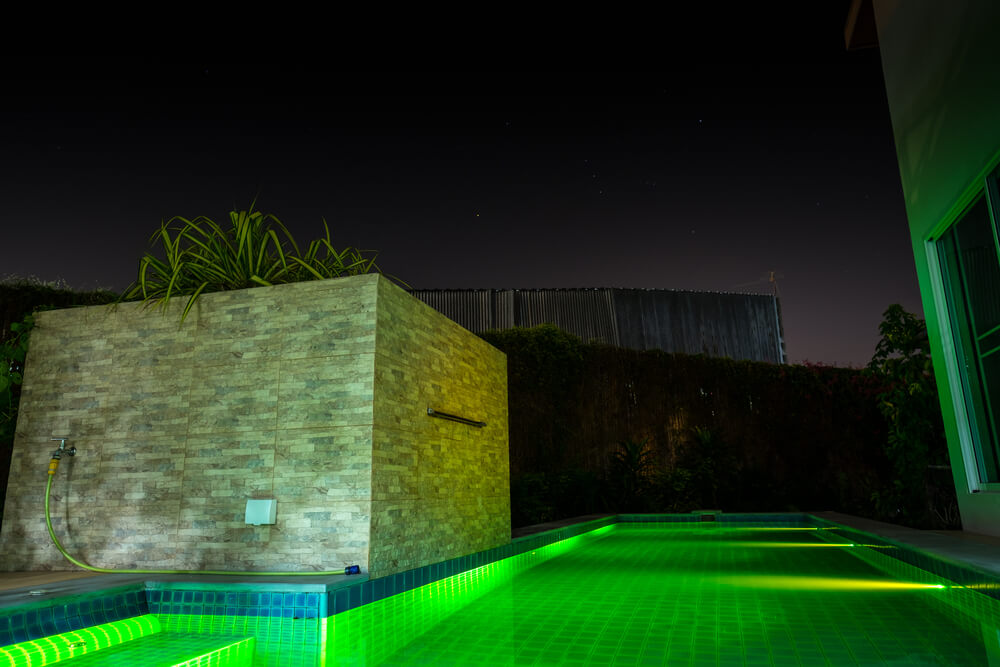 Outdoor swimming pool in the night time with Green LED light under water