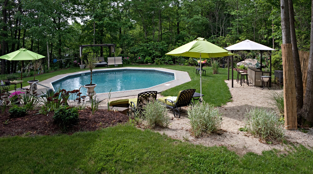 A wide angle panoramic view of a luxurious in ground pool and patio