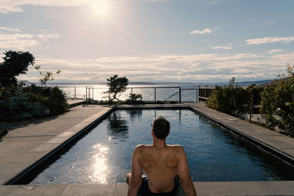 Rear View of Athletic Caucasian Male Relaxing by the Pool With Sun in Sky After Swimming Laps.