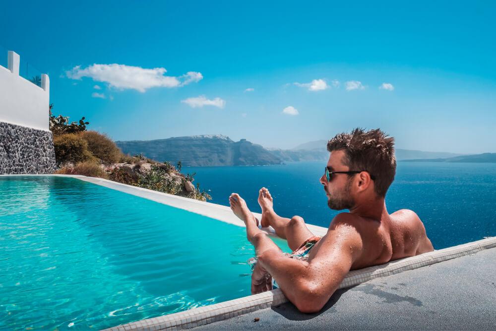Man Relaxing in Infinity Swimming Pool Looking at the Ocean