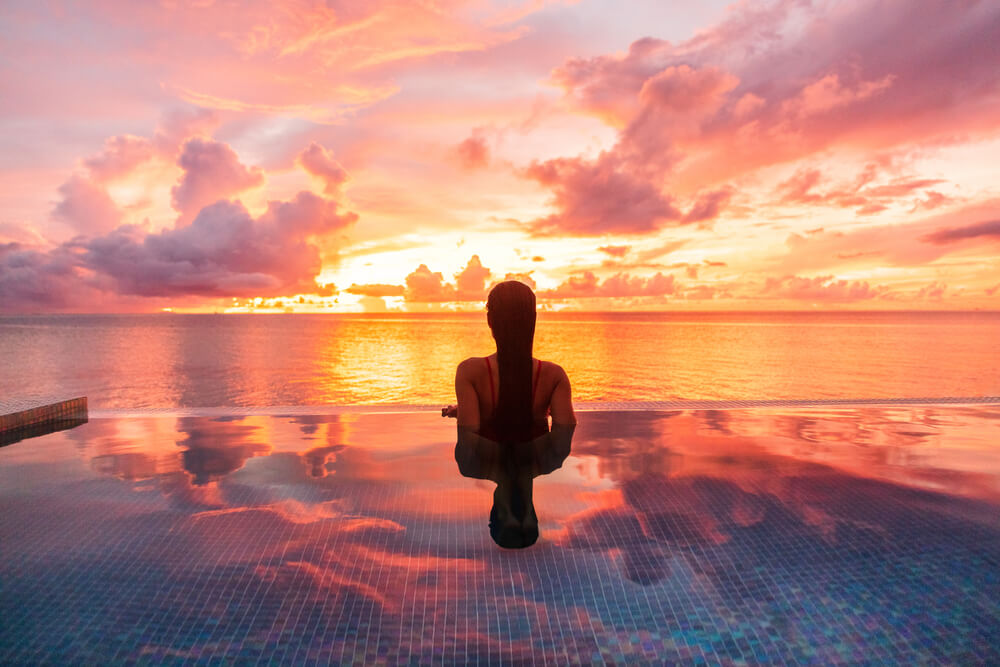 Woman Silhouette Swimming in Infinity Pool Watching Sunset Serene.