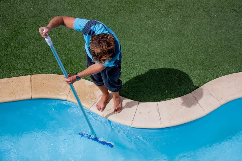 Male Pool Cleaner Cleaning a Pool