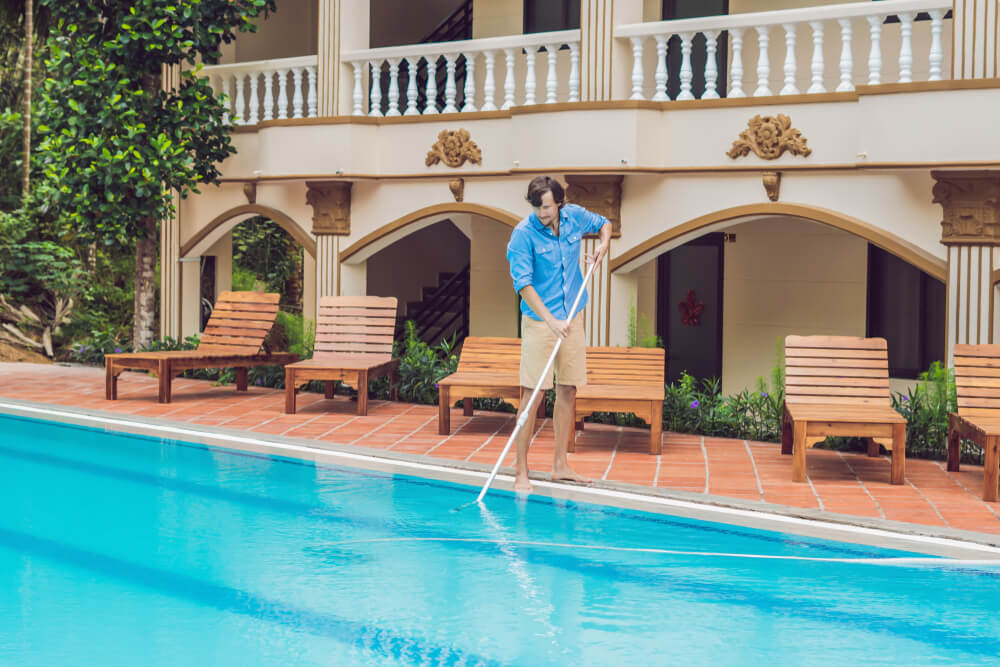 Man in a Blue Shirt With Cleaning Equipment for Swimming Pools, Sunny