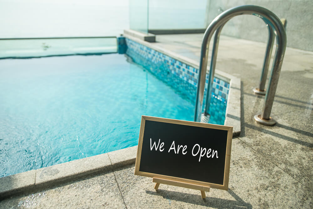 Blackboard With Text We Are Open and Swimming Pool as a Background