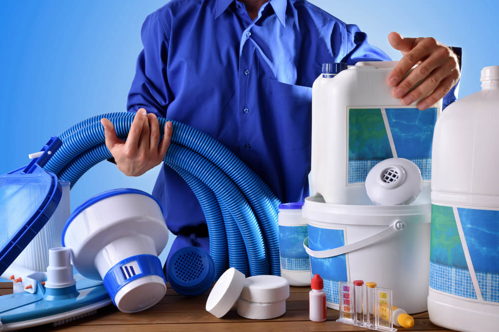 Swimming Pool Maintenance Worker With Chemical Cleaning Products and Tools on Wood Table and Blue Background